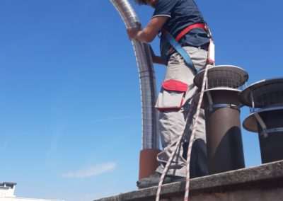 Photo d'Yves Kervazo ramoneur de la parisienne de ramonage exerçant un tubage par le toit