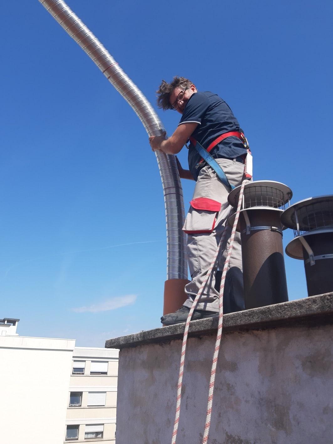 Image d'un ramoneur exerçant un tubage par le toit