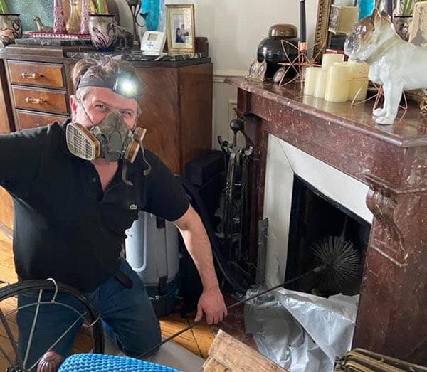 Photo d'Yves Kervazo ramonant une cheminée par le bas